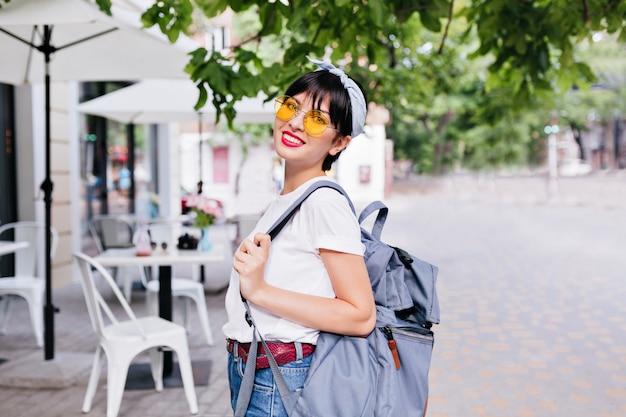 Linda garota morena sorridente com óculos escuros amarelos e cinto de couro carregando mochila enquanto explora a cidade