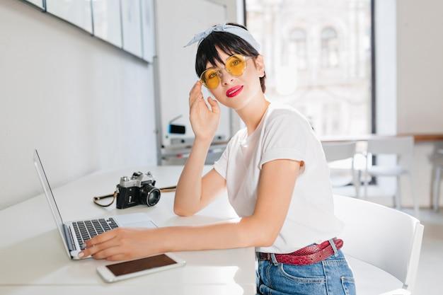 Linda garota morena usa óculos amarelos e cinto de couro, trabalhando no escritório, sentada com laptop e smartphone