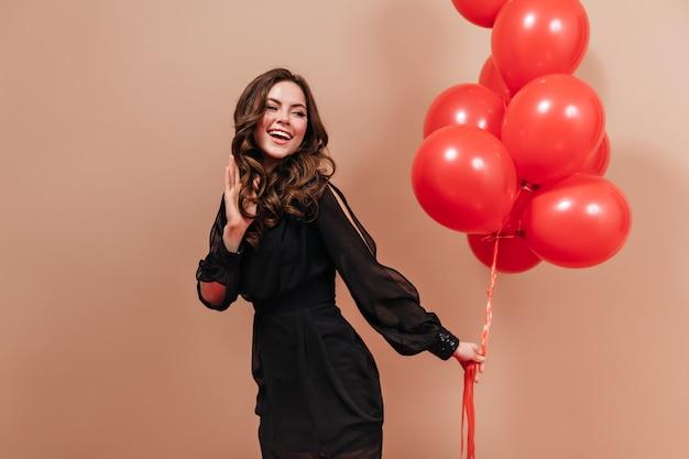 Linda garota morena vestida com roupa da moda preta, ri e posa com balões grandes.