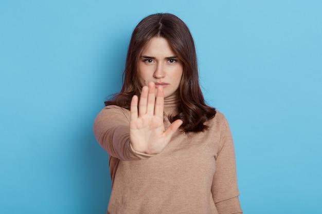Linda garota mostrando a placa de pare com as palmas das mãos e olhando diretamente para a câmera com uma expressão séria, senhora posando isolada