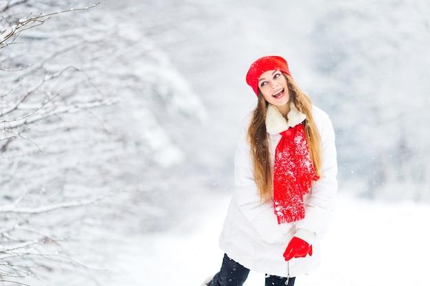Linda garota mostrando caretas em roupas de inverno brancas e vermelhas em um parque coberto de neve