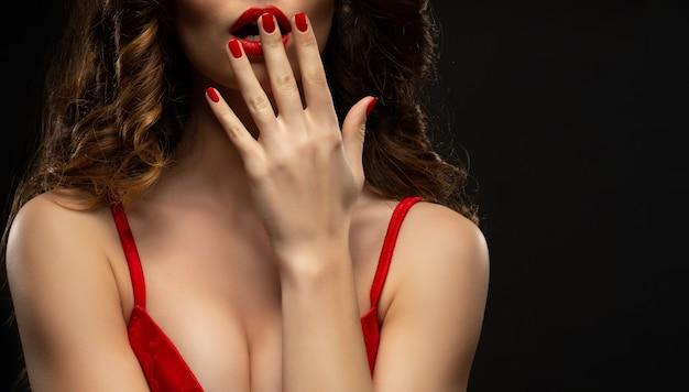 Linda garota mostrando manicure vermelha, unhas, maquiagem e cosméticos. menina morena com cabelos cacheados longos e brilhantes