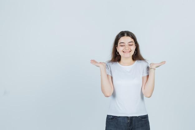 Linda garota mostrando um gesto de boas-vindas em camiseta, jeans e parece alegre. vista frontal.