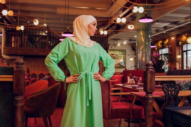Linda garota muçulmana em hijab sorrindo, esperando por sua comida em um restaurante.