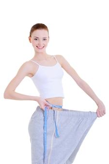 Linda garota muito jovem medindo sua cintura fina