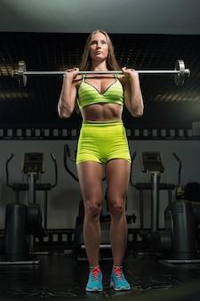 Linda garota muscular atlética sexy. garota fitness treina no ginásio, fazendo exercícios com um barbell