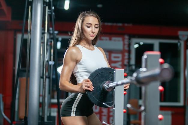 Linda garota musculosa se preparando para realizar um exercício de halterofilismo deitada em um banco
