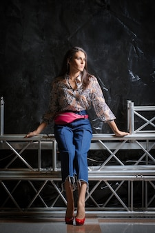 Linda garota na camisa com estampa de flor, jeans largos curtos e posando de bolsa de cintura de couro rosa