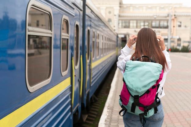 Linda garota na estação ferroviária por trás, foto