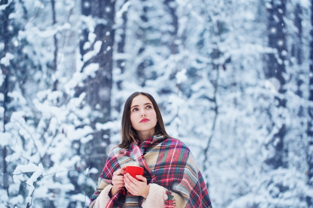 Linda garota na floresta de neve de inverno
