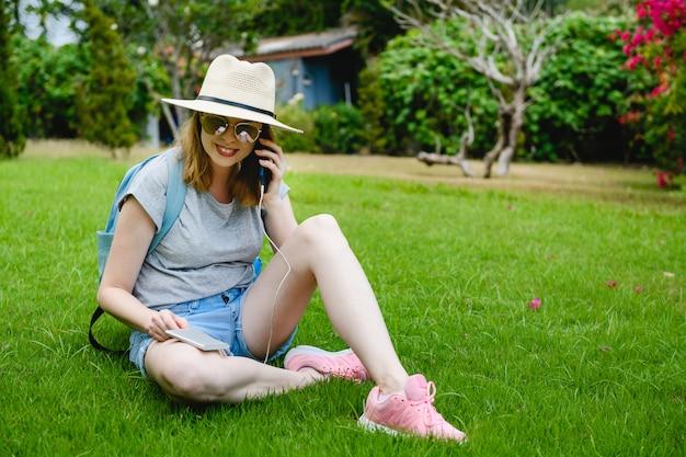 Linda garota na grama falar por smartphone