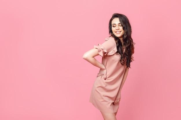Linda garota na moda com cabelo longo cacheado em um vestido rosa no estúdio em uma rosa.