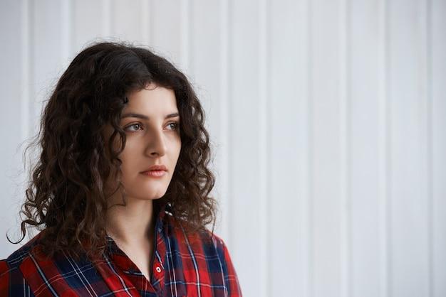 Linda garota na moda com camisa quadriculada posando Foto gratuita