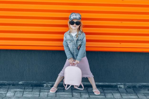 Linda garota na moda em óculos de sol pretos na saia rosa com bolsa rosa