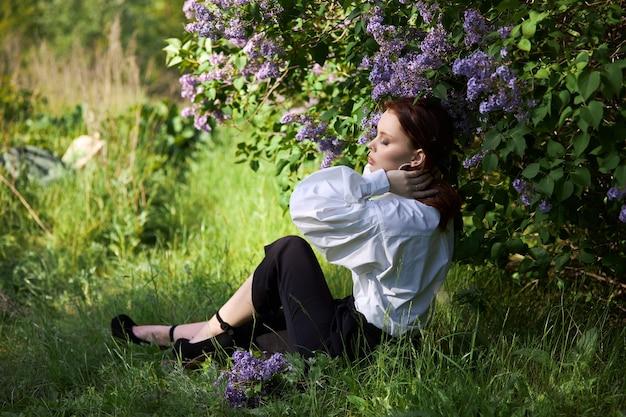 Linda garota na primavera nos galhos de arbustos de lilases em flor. retrato de uma mulher em um dia ensolarado de verão