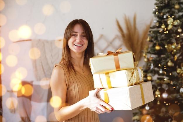 Linda garota na sala com um presente em uma embalagem de ouro perto da árvore de natal