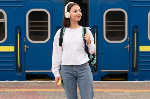 Linda garota na vista frontal da estação ferroviária