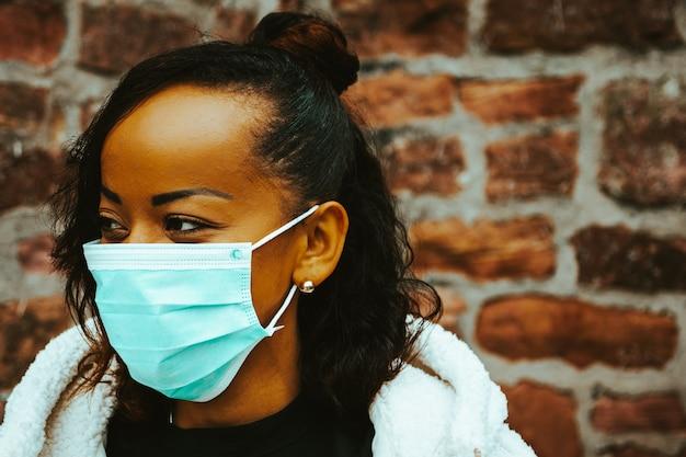 Linda garota negra ao ar livre com uma máscara médica