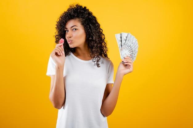 Linda garota negra com ficha de poker do casino online e dinheiro dólares isolado sobre o amarelo