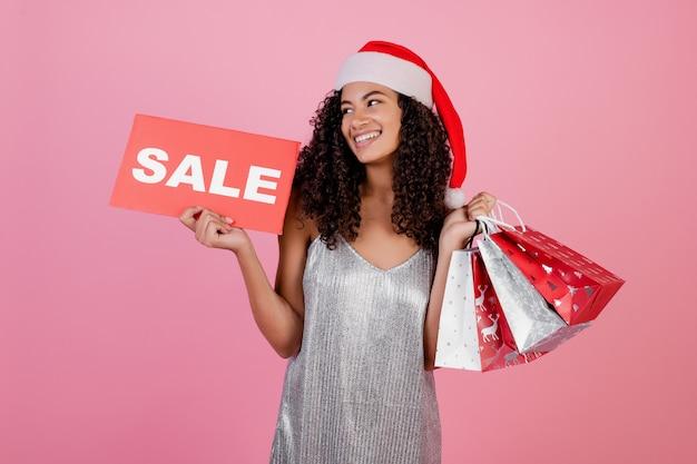 Linda garota negra com presentes em sacolas de compras de férias e sinal de venda usando chapéu de papai noel