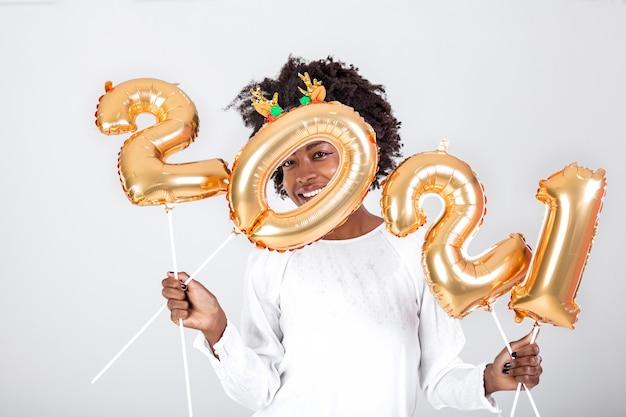 Linda garota negra festeira com cabelo encaracolado e roupas festivas posando