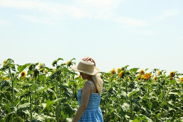 Linda garota no campo de girassol. dia ensolarado de verão