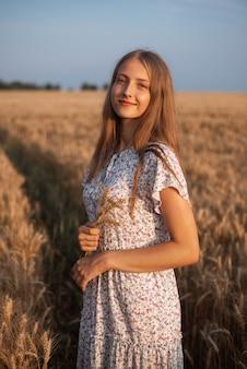 Linda garota no campo de grãos maduros iluminada pelos raios quentes dos raios do verão passado