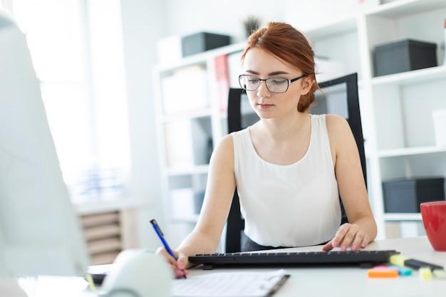 Linda garota no escritório trabalhando com caneta, documentos e computador.