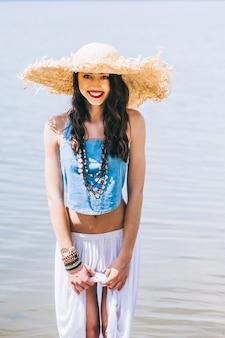 Linda garota no lago em grande chapéu