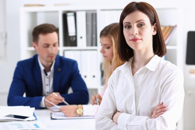 Linda garota no local de trabalho olha na câmera com grupo de colegas, mãos cruzadas. trabalhador de colarinho branco no espaço de trabalho, oferta de emprego, estilo de vida moderno, visita do cliente, conceito de trem de profissão