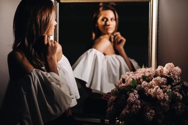 Linda garota no reflexo do espelho em casa. garota antes do feriado perto do espelho doméstico. uma garota com um vestido branco e cabelo comprido vai para uma festa em casa