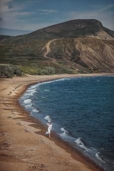 Linda garota, noiva, de vestido branco, descalça, caminhando na praia perto da água