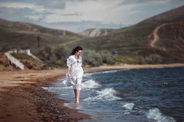 Linda garota, noiva, de vestido branco, descalça, corre na praia, na água e ri