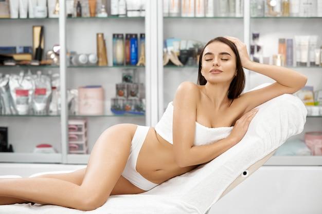 Linda garota nua em lingerie branca e toalha deitada no centro de beleza com os olhos fechados
