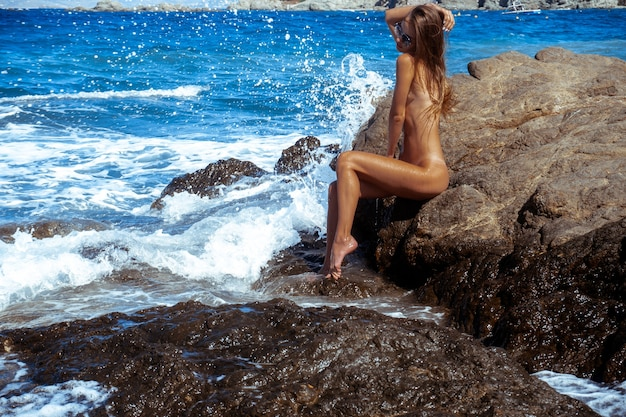 Linda garota nua em uma praia rochosa