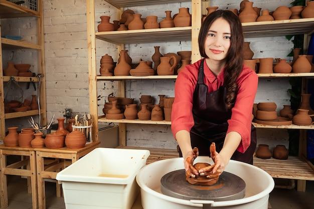 Linda garota oleiro moldes de panela de barro em mastre. uma mulher trabalha com argila em uma roda de oleiro. pote de barro nas mãos de um mestre.