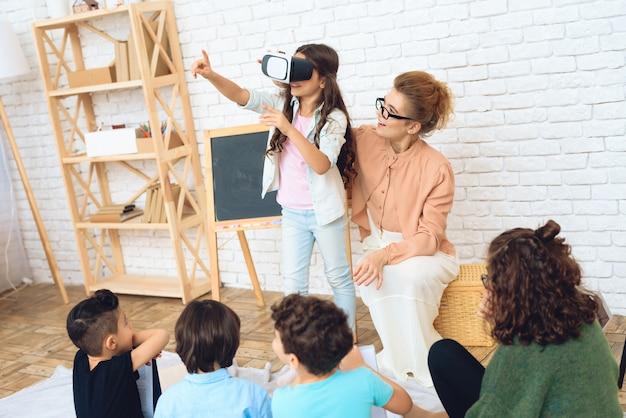 Linda garota olha para óculos de realidade virtual na sala de aula.
