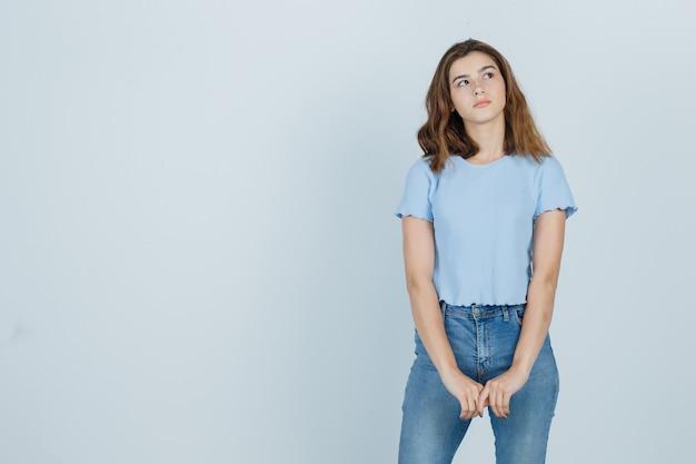 Linda garota olhando de lado em t-shirt, jeans e olhando pensativa, vista frontal.