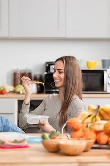 Linda garota, olhando e sorrindo para a comida dela