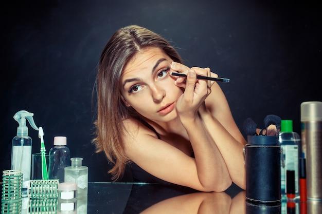 Linda garota olhando no espelho e aplicando cosméticos com um pincel grande.