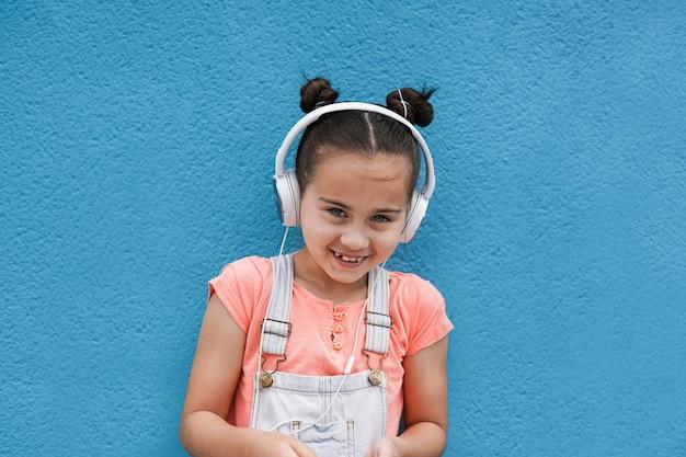 Linda garota olhando para a câmera enquanto ouve uma lista de reprodução de música com fone de ouvido - conceito de criança e tecnologia