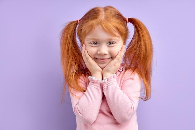 Linda garota olhando para a frente sorrindo alegremente, doce criança segurando as mãos no rosto, criança linda e engraçada com cabelo ruivo natural preso em rabo de cavalo