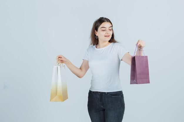Linda garota olhando para sacolas de presente em camiseta, jeans e parecendo surpresa. vista frontal.