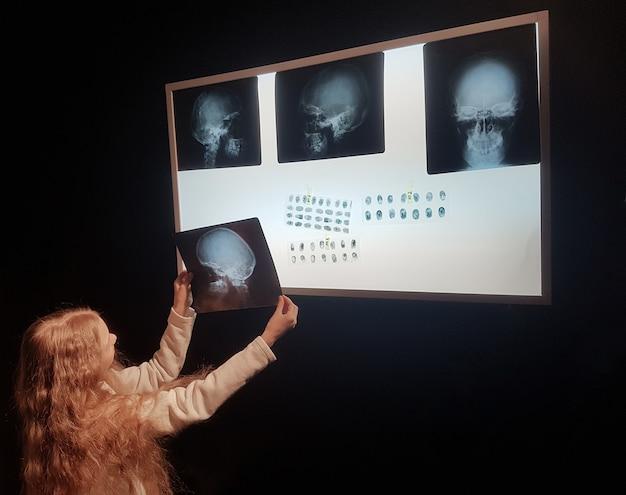 Linda garota olhando para uma foto de um crânio humano.