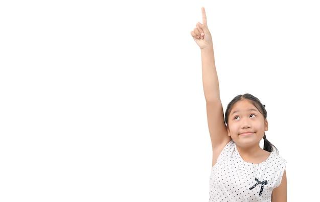 Linda garota olhou para cima enquanto apontava o dedo para cima, isolado no fundo branco, copie o espaço