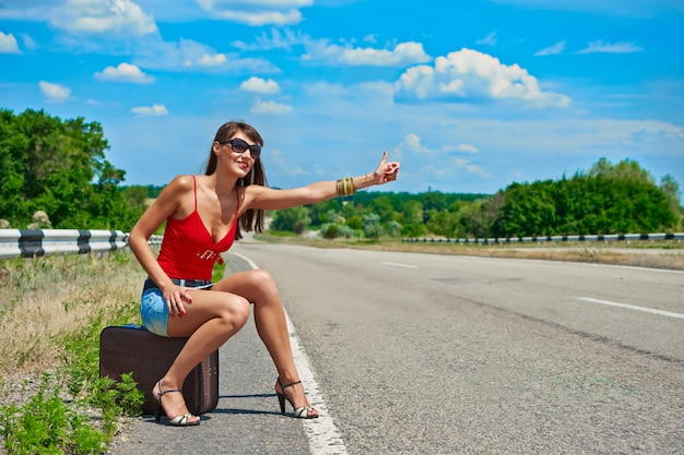 Linda garota ou mulher em mini com mala pedindo carona ao longo de uma estrada