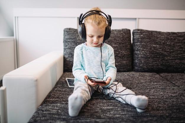 Linda garota ouvindo música no sofá