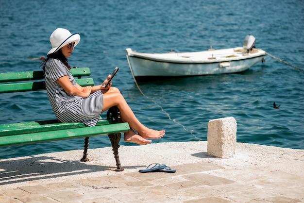 Linda garota parece fotos em um tablet e sorri.