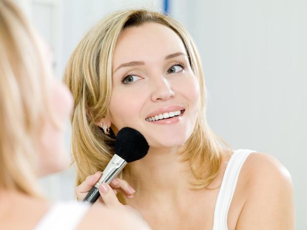 Linda garota passa pó no rosto com um pincel para maquiagem - dentro de casa