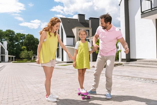 Linda garota patinando enquanto está junto com os pais